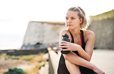 Young sporty woman runner with water bottle sitting outside, resting. Copy space.