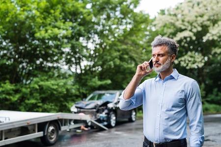 Uomo maturo che fa una telefonata dopo un incidente d'auto. Copia spazio. Archivio Fotografico