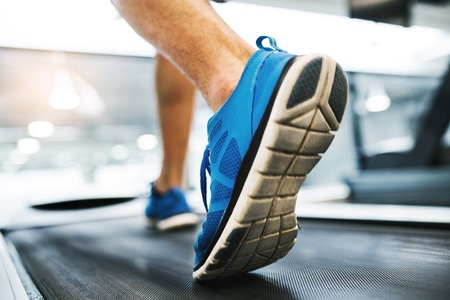 Feet of young man in gym running on treadmill.