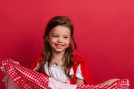 Een klein meisje in Little Red Riding Hood kostuum in studio op een rode achtergrond. Stockfoto
