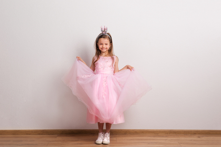 Happy small princess girl with crown headband in studio on a white background. Stock Photo