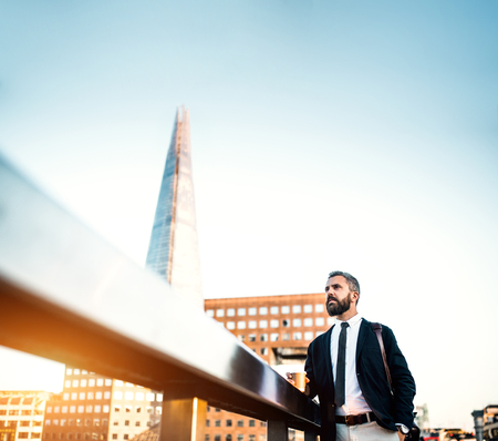 Hipster businessman with coffee standing on the bridge in London. Copy space.