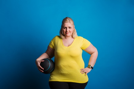 Portrait of a happy overweight woman with smartwatch and heavy ball in studio.