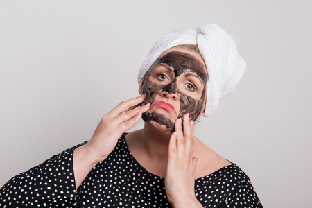 A sad overweight woman with black facial mask on her face in a studio.
