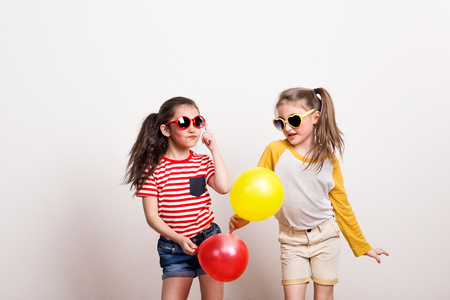 Small girls with sunglasses and balloons standing in a studio.