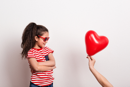 A small girl with red sunglasses and striped T-shirt looking at red heart balloon. Stock fotó