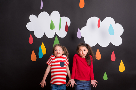 Small girls in studio, standing against black background with clouds and raindrops. 免版税图像