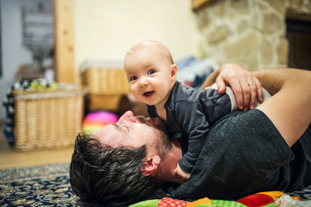 Father lying down on the floor with a baby girl at home. Banco de Imagens