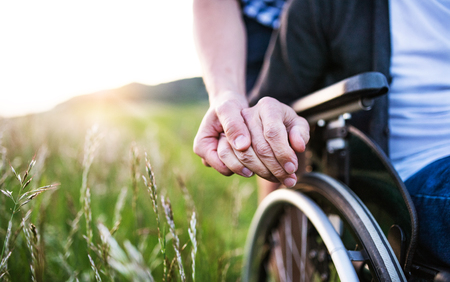 A close-up of unrecognizable son holding his fathers hand on a wheelchair.
