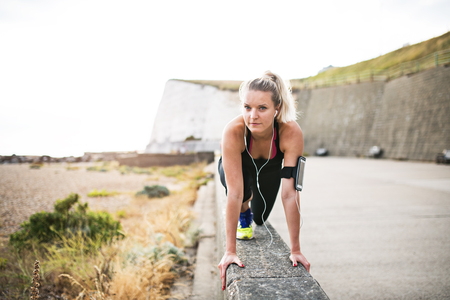 Young sporty woman runner with earphones stretching outside in nature.