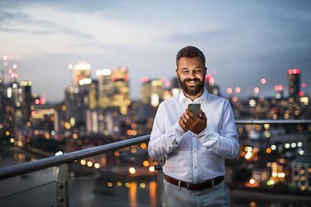 Een zakenman met smartphone die zich tegen de meningspanorama van Londen bevindt.