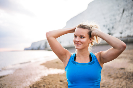 Young sporty woman runner in blue sportswear standing on the beach outside.