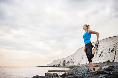 Young sporty woman runner with earphones stretching on the beach outside.