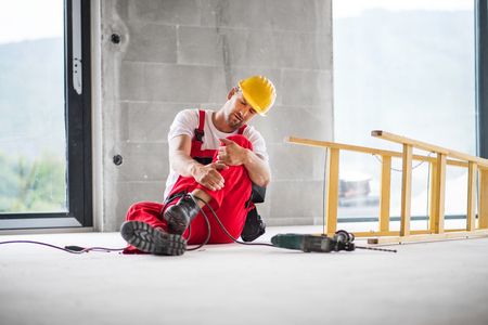 An accident of a man worker at the construction site. Reklamní fotografie