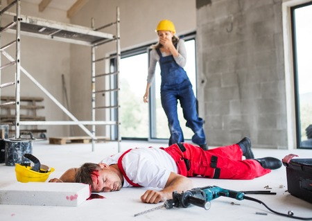 A woman found man worker lying unconscious on the floor at the construction site. Banque d'images - 107931560
