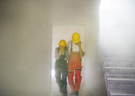 Woman and man workers suffocating at the construction site. Фото со стока