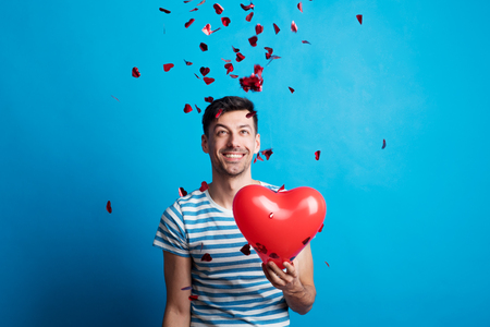 A young man in love holding red heart, confetti falling on him.