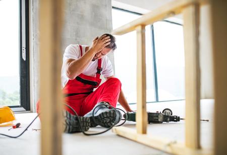 Een ongeval van een arbeidersarbeider op de bouwplaats.