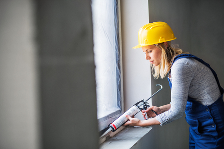 Young woman worker using silicone sealant gun on the construction site.