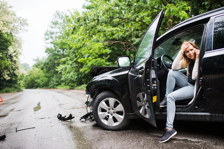 Young woman in the damaged car after a car accident, making a phone call. 스톡 콘텐츠