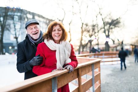 Senior paar op een wandeling in een stad in de winter. Stockfoto