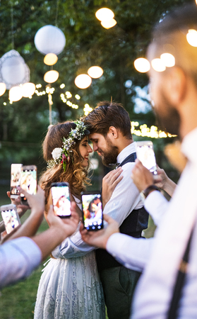 Guests with smartphones taking photo of bride and groom at wedding reception outside. Stockfoto
