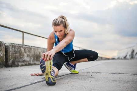 Young sporty woman runner with earphones stretching outside. Stock Photo