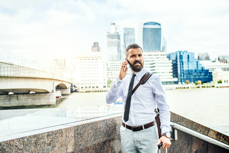 Hipster businessman with smartphone standing by the river in London, calling.
