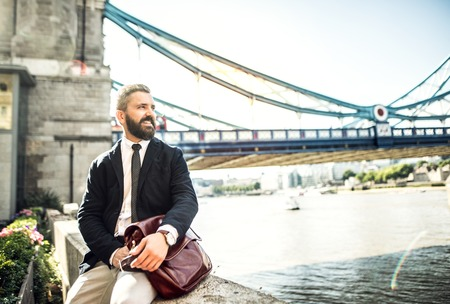 Hipster businessman with a bag sitting by the Tower Bridge in London.