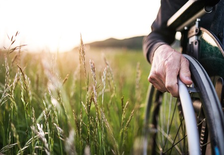 A close-up of mans hand on a wheelchair in nature at sunset. Copy space.