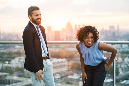 Two businesspeople standing against London rooftop view at sunset, laughing.