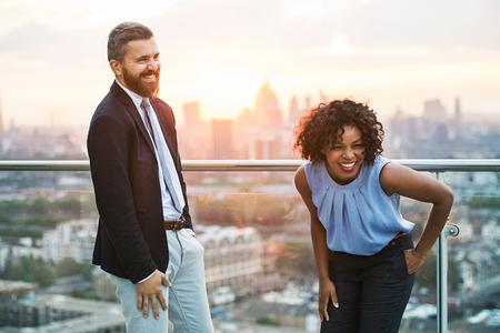 Dos empresarios de pie contra la vista de la azotea de Londres al atardecer, riendo.
