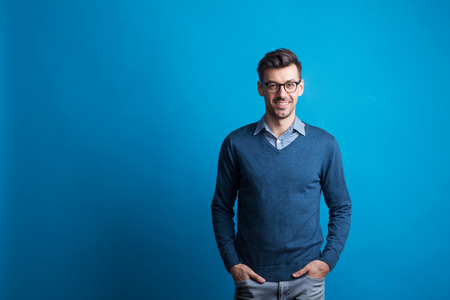 Portrait of a young man with glasses in a studio on a blue background.