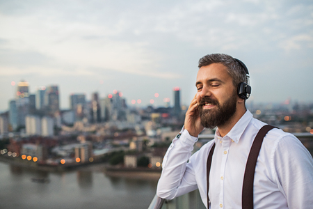 A businessman with headphones standing against London view panorama.