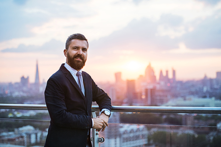 Businessman with jacket standing against London view panorama at sunset. Stock Photo