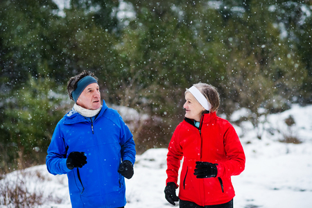 A front view of senior couple jogging in snowy winter nature. Stockfoto
