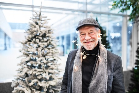 Portrait of senior man in shopping center at Christmas time, chain of light around head.