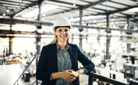 Portret inżyniera przemysłowego kobiety stojącej w fabryce. Zdjęcie Seryjne