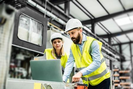 Een portret van een industriële man en vrouw ingenieur met laptop in een fabriek, aan het werk.