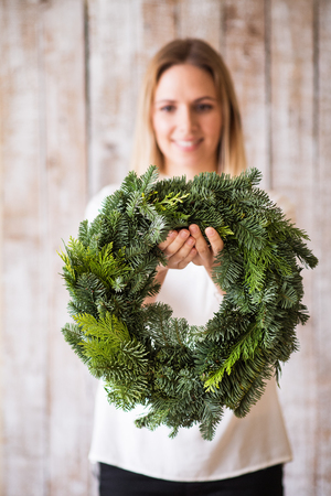 A young woman holding green Christmas wreath.