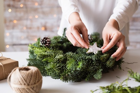 Hands of unrecognizable woman decorating christmas wreath. Banque d'images