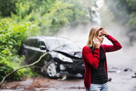 Una mujer joven con un teléfono inteligente junto al automóvil dañado después de un accidente automovilístico, haciendo una llamada telefónica.