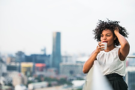 A close-up portrait of a woman standing on a terrace, drinking coffee.