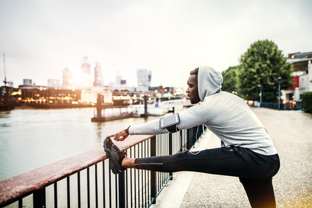 Black man runner with smartphone in an armband on the bridge in a city, stretching.