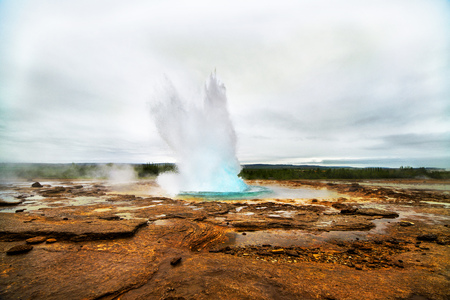 Geyser eruption in a beautifil Iceland landscape, Europe.
