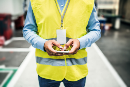 An unrecognizable industrial man engineer with name tag in a factory, using smartphone. Copy space. Banque d'images