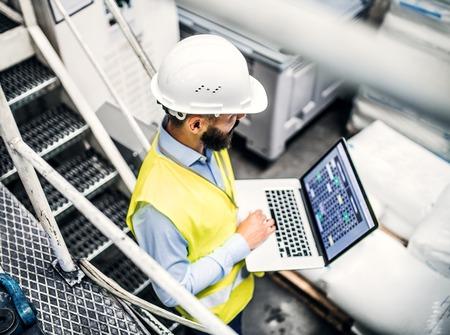 Ein Porträt eines Industriemanningenieurs mit Laptop in einer Fabrik, die arbeitet. Standard-Bild - 108764513