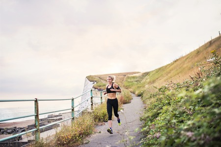 Young sporty woman runner with earphones running by sea in nature.