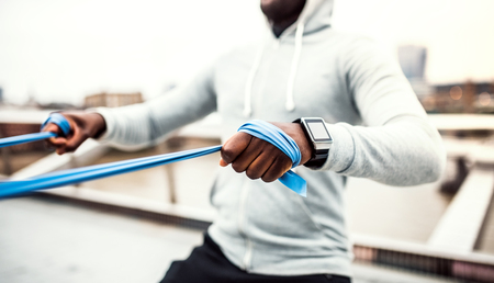 Young black sportsman exercising with elastic rubber bands in London. Banque d'images