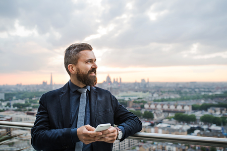 A portrait of businessman with smartphone standing against London view panorama. Stock Photo